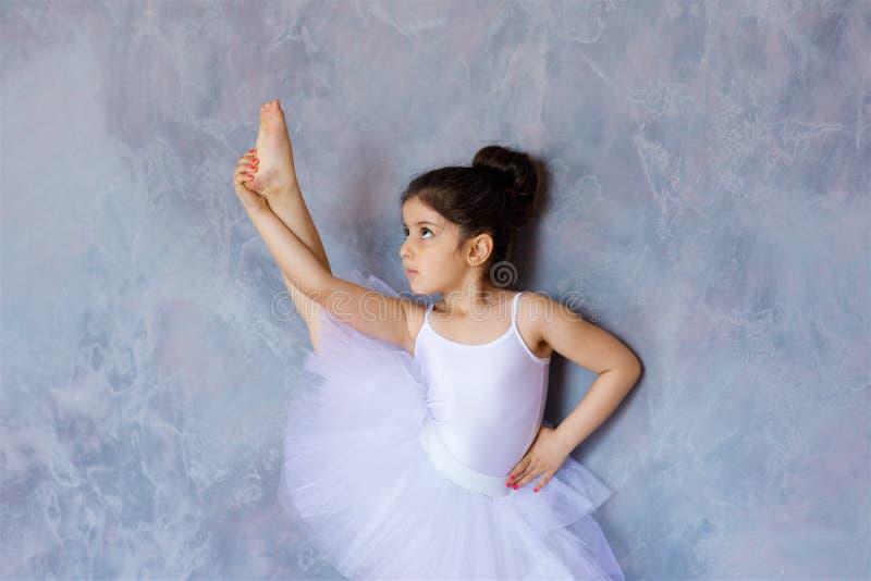 Wenig Mädchenballerina in einem weißen Ballettröckchen stockbild