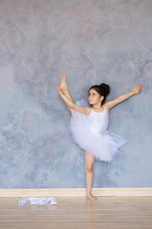 Wenig Mädchenballerina in einem weißen Ballettröckchen stockbilder