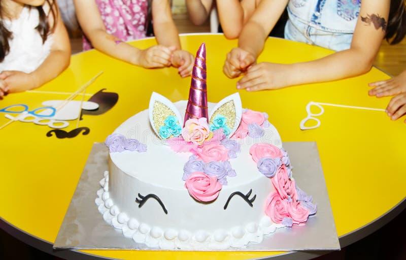 Wenig Mädchengeburtstagsfeiertabelle mit Einhornkuchen lizenzfreies stockfoto