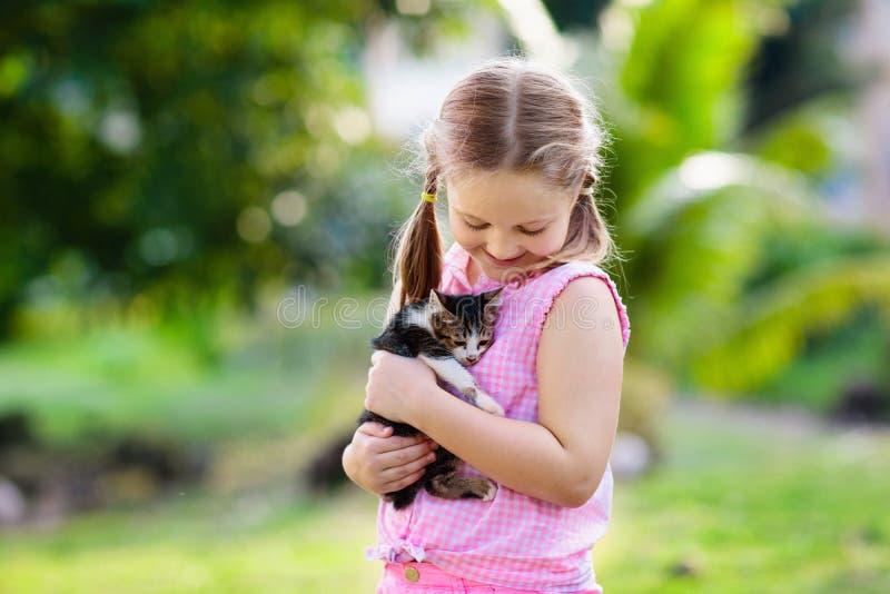 Wenig Mädchenholdingbabykatze Kinder und Haustiere lizenzfreie stockbilder