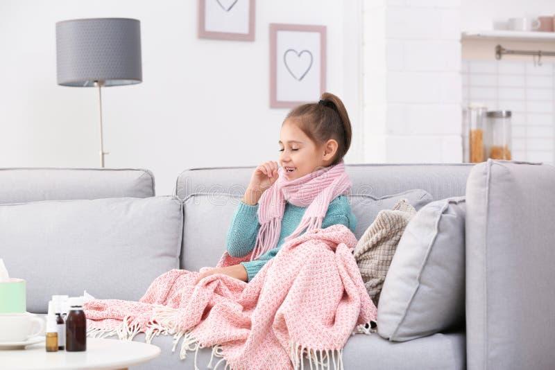 Wenig Mädchenleiden vom Husten und Kälte auf Sofa lizenzfreie stockbilder