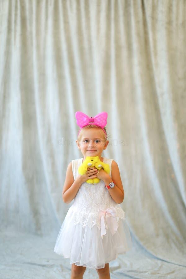 Wenig Mädchenstellung mit Spielzeug am Fotostudio stockbild