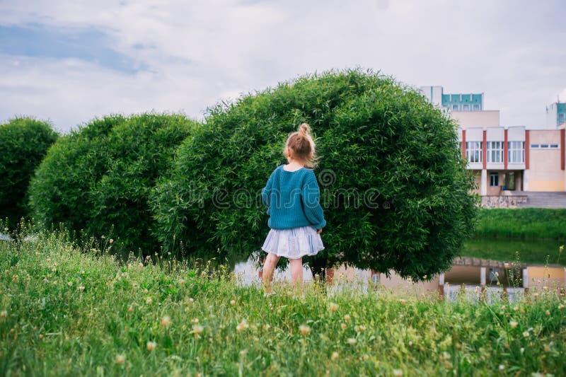 Wenig Mädchenweg im Gras auf der Stadt PAK nahe Teich R?ckseitige Ansicht lizenzfreies stockfoto