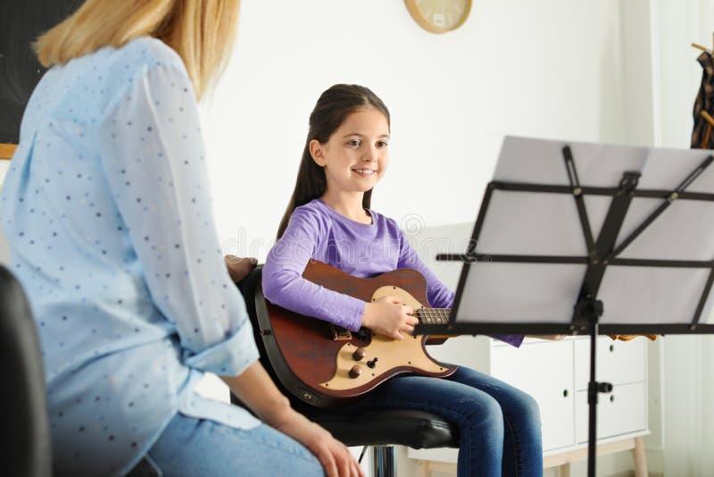 Wenig M?dchen, das Gitarre mit ihrem Lehrer am Musikunterricht spielt lizenzfreie stockfotografie