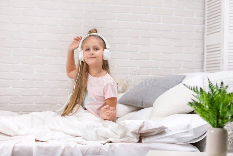 Wenig M?dchen, das Musik mit den Kopfh?rern auf Bett h?rt stockfotos