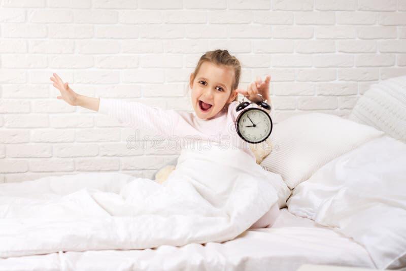 Wenig M?dchen in den Pyjamas mit Uhr stockfotografie