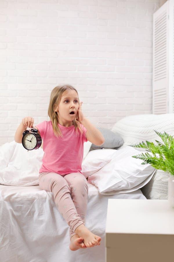Wenig M?dchen in den Pyjamas mit Uhr lizenzfreie stockbilder
