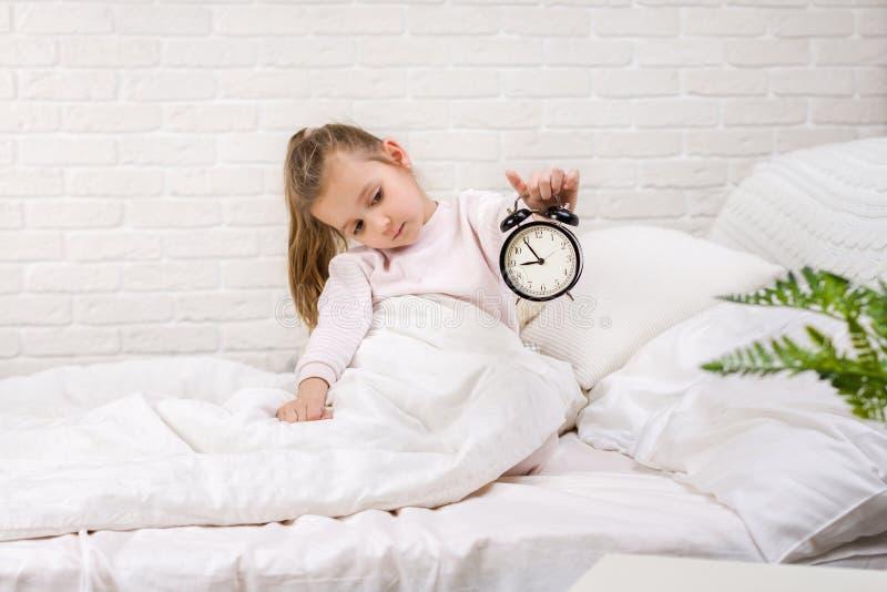 Wenig M?dchen in den Pyjamas mit Uhr lizenzfreies stockbild