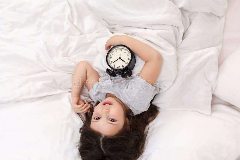 Wenig M?dchen in den Pyjamas mit Uhr lizenzfreies stockfoto