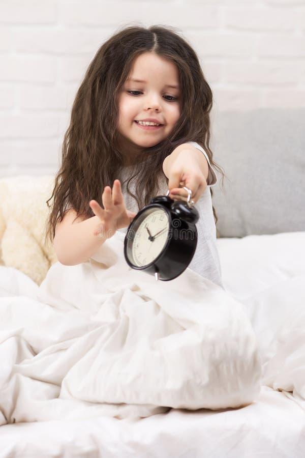 Wenig M?dchen in den Pyjamas mit Uhr lizenzfreie stockfotografie