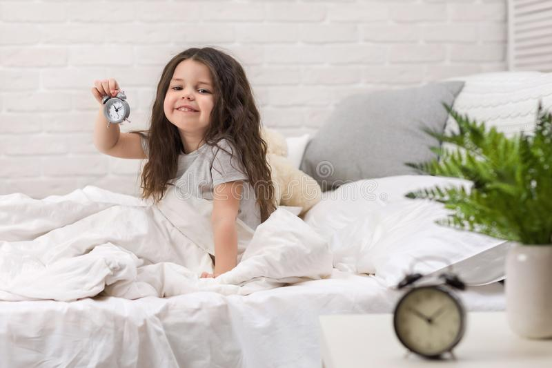Wenig M?dchen in den Pyjamas mit Uhr stockfoto