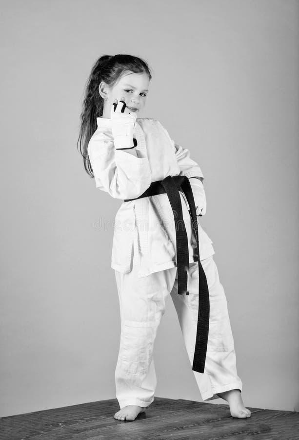 wenig M?dchen in der Gisportkleidung ?bendes Kung Fu Gl?ckliche Kindheit Sporterfolg im Einzelkampf kleines M?dchen in Kriegs lizenzfreie stockfotos
