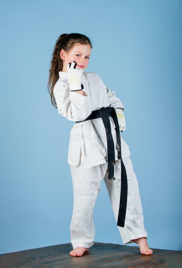 wenig M?dchen in der Gisportkleidung ?bendes Kung Fu Gl?ckliche Kindheit Sporterfolg im Einzelkampf kleines M?dchen in Kriegs stockfotos