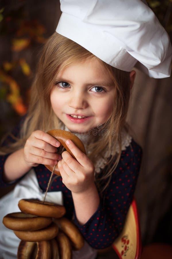 Wenig M?dchen in der Kochkleidung mit Bageln in ihren H?nden und in L?cheln stockfotos