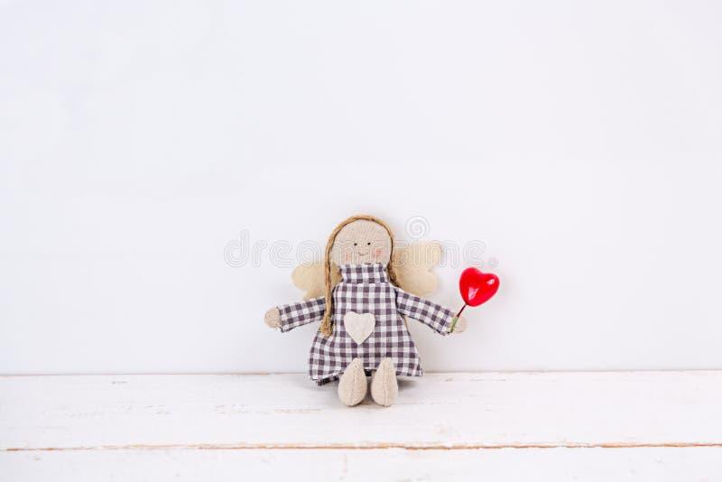 Wenig Marionette mit einem roten Herzen, das auf einem hölzernen weißen Hintergrund sitzt lizenzfreie stockfotos