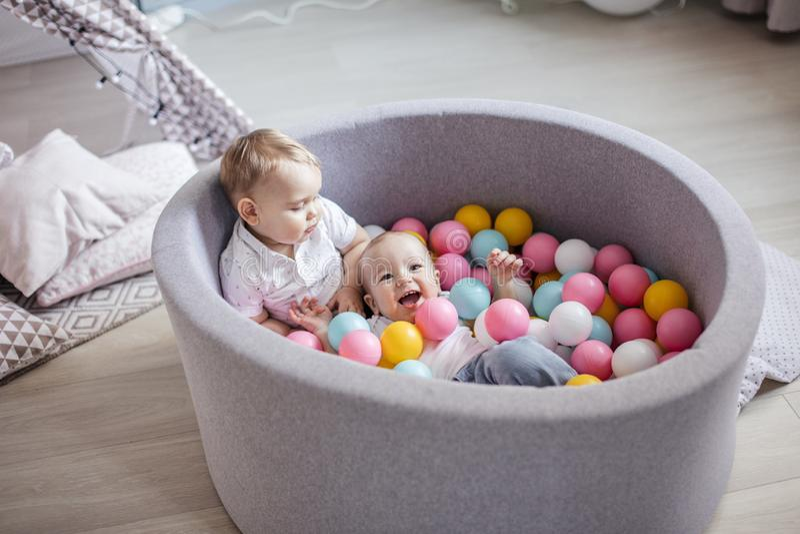 Wenig nette glückliche Kinder spielen mit Bällen in der Ballgrube im Spielraum Zeit, f?r das sch?ne, l?chelnde junge Afroamerikan stockbild