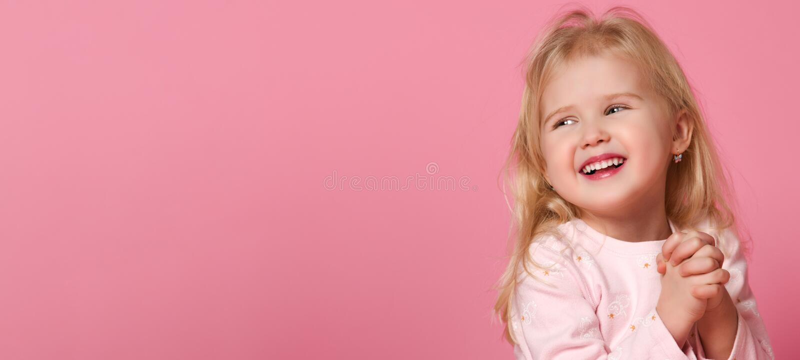 Wenig nette M?dchenkinderblondine in einer rosa Klage ist auf einem rosa Hintergrund sch?chtern lizenzfreies stockfoto
