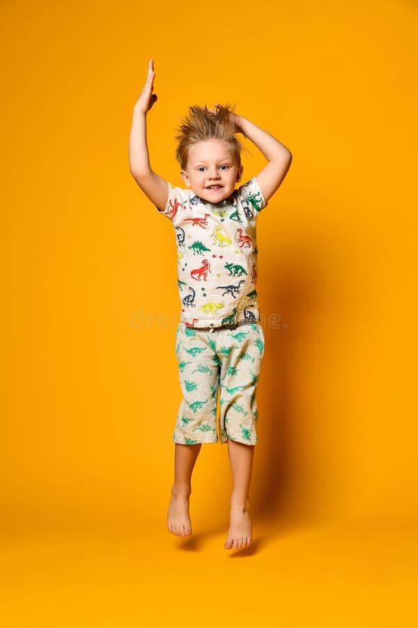 Wenig netter blonder Jungenvorschüler in den Pyjamas mit den Dinosauriern, die Spaß haben, hat Freude im Studio über gelbem Hinte stockfoto
