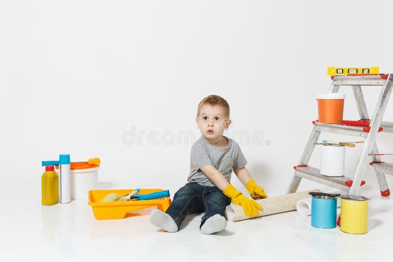 Wenig netter Junge in den gelben Handschuhen mit Instrumenten für den Erneuerungswohnungsraum lokalisiert auf weißem Hintergrund  lizenzfreie stockbilder