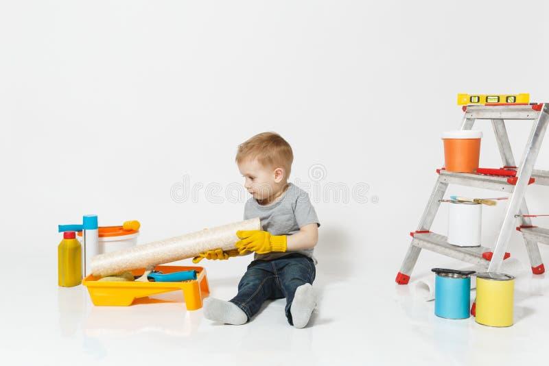 Wenig netter Junge in den gelben Handschuhen mit Instrumenten für den Erneuerungswohnungsraum lokalisiert auf weißem Hintergrund  lizenzfreie stockfotografie