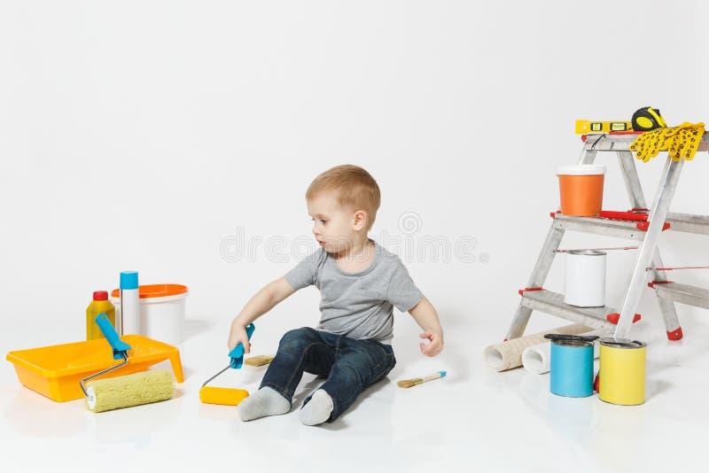 Wenig netter Junge, der auf Boden mit Instrumenten für den Erneuerungswohnungsraum lokalisiert auf weißem Hintergrund sitzt tapet stockfoto