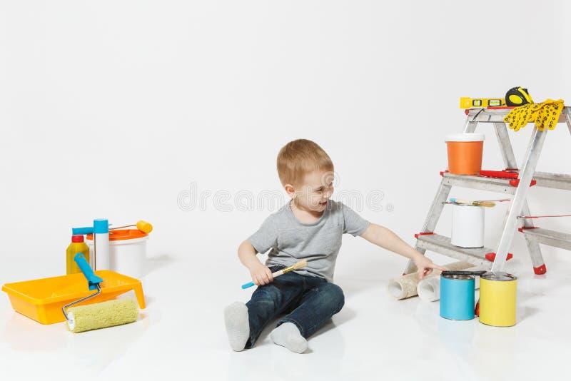 Wenig netter Junge, der auf Boden mit Instrumenten für den Erneuerungswohnungsraum lokalisiert auf weißem Hintergrund sitzt tapet stockfotografie
