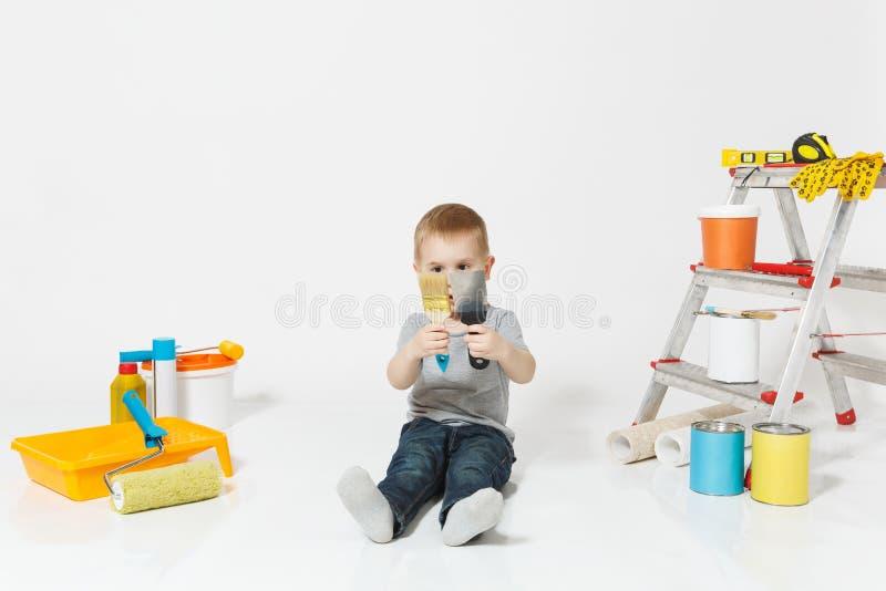 Wenig netter Junge, der auf Boden mit Instrumenten für den Erneuerungswohnungsraum lokalisiert auf weißem Hintergrund sitzt tapet lizenzfreie stockbilder