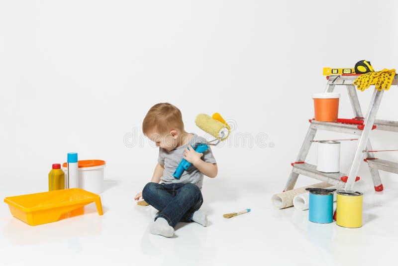 Wenig netter Junge, der auf Boden mit Instrumenten für den Erneuerungswohnungsraum lokalisiert auf weißem Hintergrund sitzt tapet stockbilder
