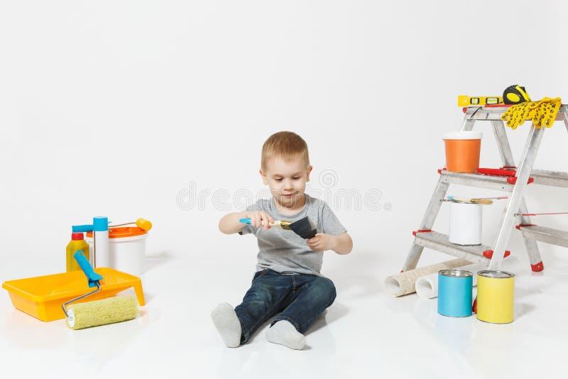 Wenig netter Junge, der auf Boden mit Instrumenten für den Erneuerungswohnungsraum lokalisiert auf weißem Hintergrund sitzt tapet lizenzfreies stockfoto