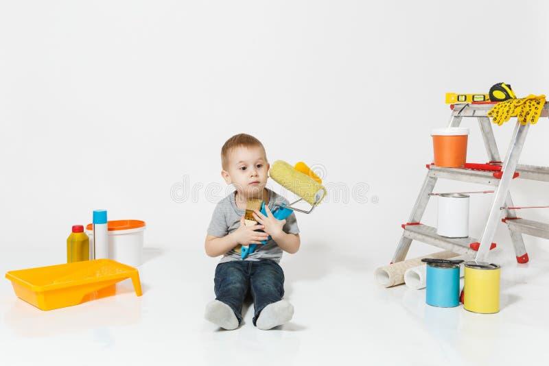 Wenig netter Junge, der auf Boden mit Instrumenten für den Erneuerungswohnungsraum lokalisiert auf weißem Hintergrund sitzt tapet stockbild