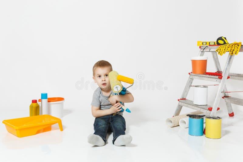 Wenig netter Junge, der auf Boden mit Instrumenten für den Erneuerungswohnungsraum lokalisiert auf weißem Hintergrund sitzt tapet lizenzfreie stockfotos