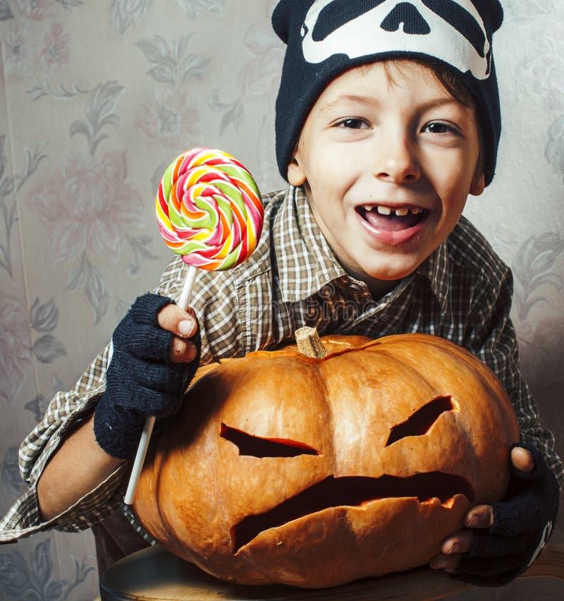 Wenig netter Junge im Skeletthut mit Kürbis und Süßigkeit am Halloween-Parteifeiertag, Lebensstilleutekonzept stockbilder