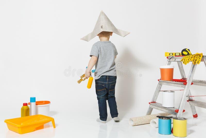 Wenig netter Junge im Zeitungshut mit Instrumenten für den Erneuerungswohnungsraum lokalisiert auf weißem Hintergrund tapete lizenzfreie stockbilder