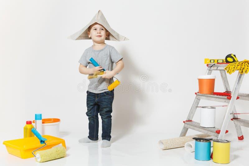 Wenig netter Junge im Zeitungshut mit Instrumenten für den Erneuerungswohnungsraum lokalisiert auf weißem Hintergrund tapete lizenzfreie stockfotografie