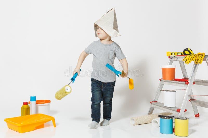 Wenig netter Junge im Zeitungshut mit Instrumenten für den Erneuerungswohnungsraum lokalisiert auf weißem Hintergrund tapete lizenzfreie stockfotos