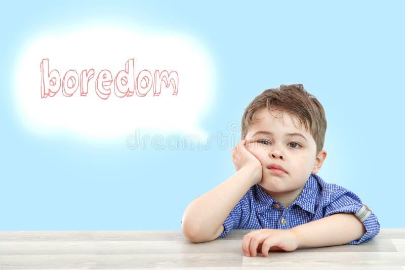 Wenig netter Junge sitzt und denkt Langeweile auf hellem lokalisiertem Hintergrund stockfoto