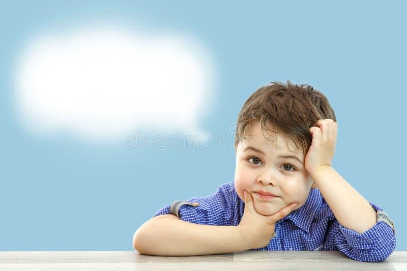 Wenig netter Junge und seine Wolke von Gedanken auf lokalisiertem Hintergrund lizenzfreies stockfoto