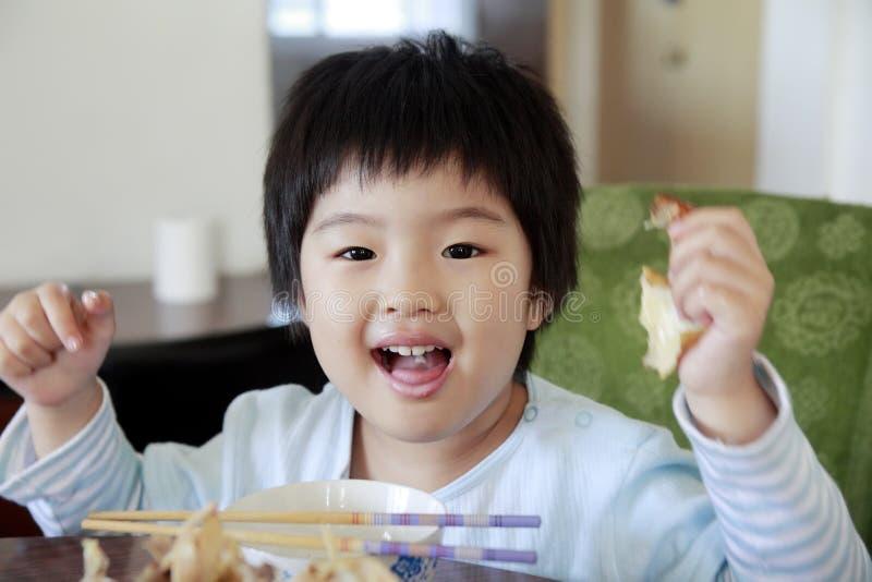 Wenig nettes asiatisches Mädchenessen lizenzfreies stockfoto
