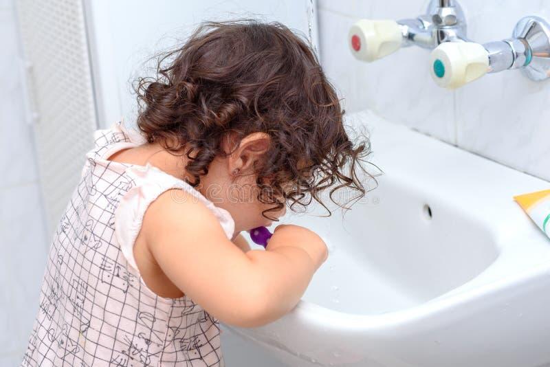 Wenig nettes Baby, das ihre Zähne mit Zahnbürste im Badezimmer säubert lizenzfreie stockbilder