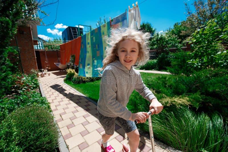 Wenig nettes blondes Mädchen, das einen Roller auf gepflasterte Wege an einem sonnigen Sommertag reitet lizenzfreie stockfotografie
