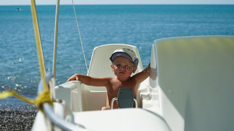 Wenig nettes entzückendes Baby sitzt im Boot auf dem Seeufer lizenzfreies stockfoto