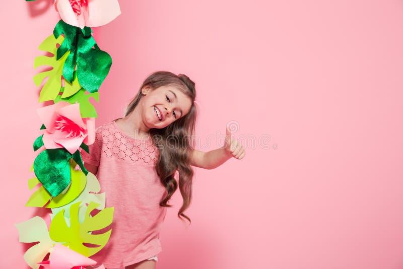 Wenig nettes Mädchen auf Farbhintergrund mit Blumen stockfoto