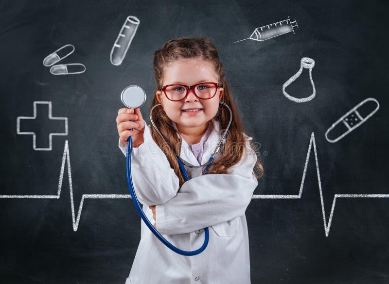 Wenig nettes Mädchen in Doktorkostüm, das sthetoscope auf Tafel hält stockbilder