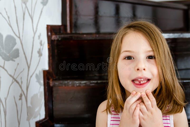 Wenig nettes Mädchen mit dem ersten verlorenen Milchzahn stockfotos
