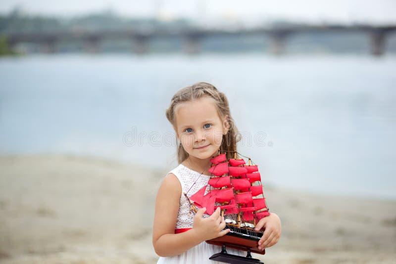 Wenig nettes Mädchen und Scharlachrot Segel Nahaufnahmeporträt des Gesichtes des Mädchens Wartezeitboot des kleinen Mädchens mit  lizenzfreies stockfoto