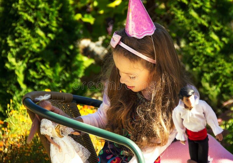 Wenig nettes Mädchenspiel mit ihrer Puppe stockfotografie