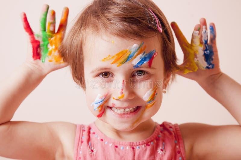 Wenig nettes M?dchen mit dem bunten Make-up der Kinder, das gemalte H?nde zeigt Bunte Zeichen auf wei?em Hintergrund lizenzfreie stockfotografie