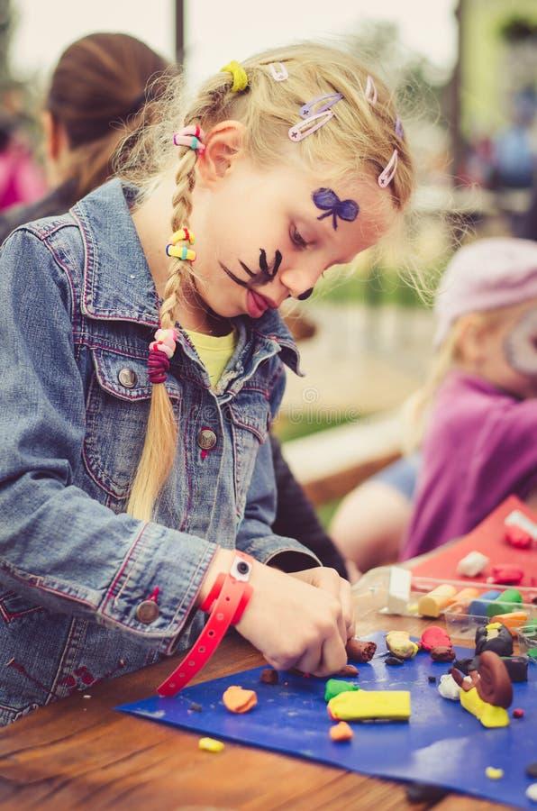 Wenig reizendes Kinderspielen mit Spielteig lizenzfreie stockfotos