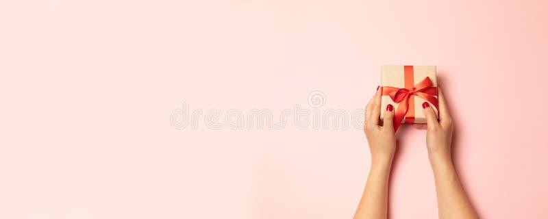 Wenig rosa Gartennelke auf einem weißen Hintergrund und der Hand einer Frau mit einem Geschenk in einem Kästchen, Raum für Text,  stockfotografie