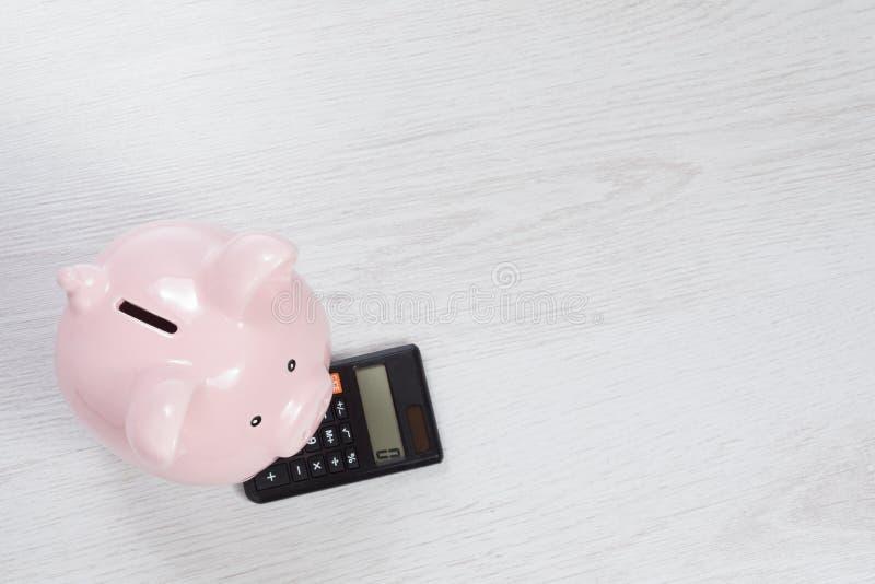 Wenig rosa Sparschwein, das auf einem Taschenrechner steht lizenzfreie stockfotografie
